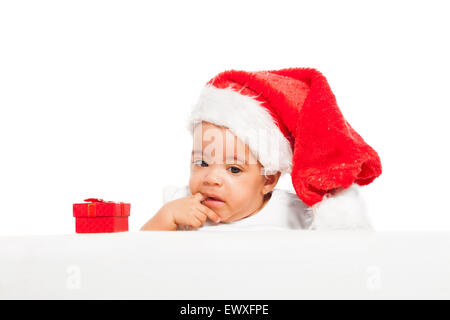 African baby paci finger wearing red Christmas hat - Stock Photo