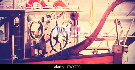 Retro vintage filtered photo of old sailing boat bridge with wooden steering wheel. - Stock Photo