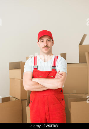 young confident delivery man standing, holding hands crossed against his chest, with cardboard boxes in background - Stock Photo