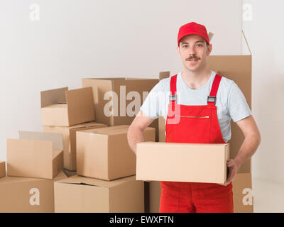 young caucasian deliveryman standing in warehouse, holding parcel - Stock Photo