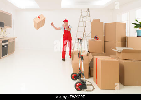 deliveryman unloading cardboard boxes into new house - Stock Photo