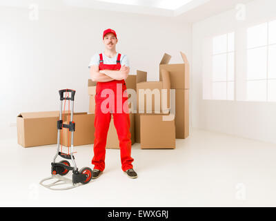 young confident delivery man standing in new home, holding hands crossed against his chest, with cardboard boxes - Stock Photo