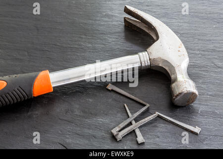 Old Steel claw hammer on slate with 5 cut nails - Stock Photo