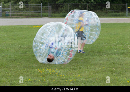 Two children having fun playing bumper balls at the Cannington Canada day Festival - Stock Photo