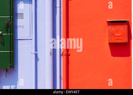 Brightly painted wall with postbox gas services and pipes Burano Venetian Lagoon Veneto Italy Europe - Stock Photo