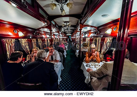 Passengers having dinner in a pillared pre-1940s dining car on the luxury Rovos Rail train between Pretoria and - Stock Photo