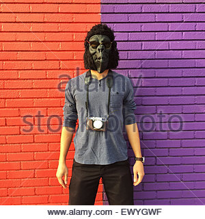 Man wearing a gorilla mask with a camera around his neck standing against a colorful brick wall - Stock Photo