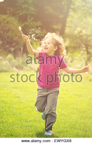 Girl running in the garden with a dandelion seedhead - Stock Photo