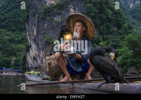 Cormorant fisherman on a raft holding a lantern, Guilin, China - Stock Photo
