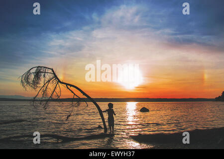 Boy standing on a log at the beach at  sunset - Stock Photo