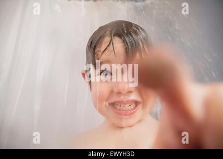 Boy in the shower pointing - Stock Photo