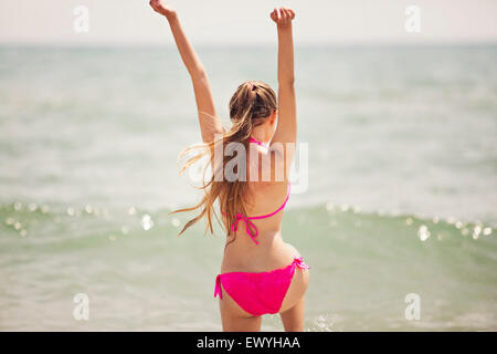 Teenage girl jumping up in the air on the beach - Stock Photo