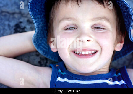 Overhead view of a boy lying on the ground with his hands behind his head - Stock Photo