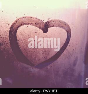 Heart drawn on a wet window - Stock Photo