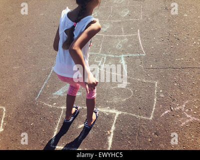Girl Playing Hopscotch - Stock Photo