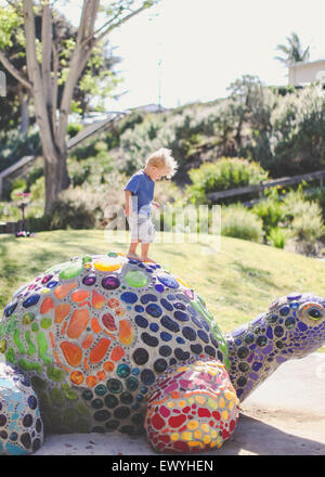 Boy standing on a mosaic turtle, Laguna Beach, Orange County, California, USA - Stock Photo