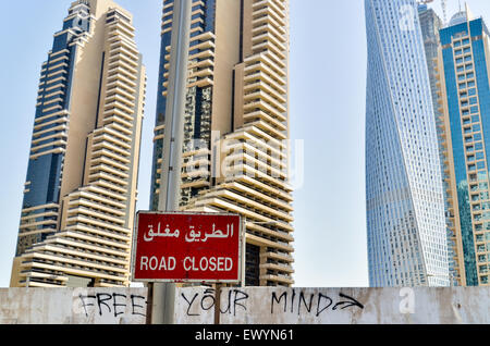 'Free your mind' written on a wall of a road in construction near the Dubai Marina, UAE - Stock Photo