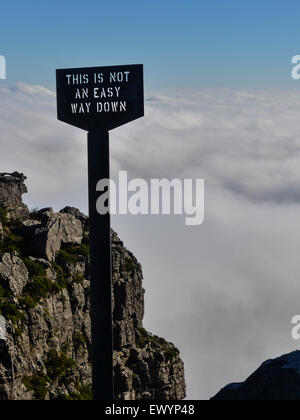 Sign reading 'This is not an easy way down' at the edge of Table Mountain, Cape Town, in front of a carpet of white - Stock Photo