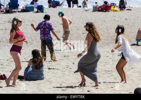 San Luis Obispo, California - young adults having fun and dancing on the beach wearing headphones in a hush concert, - Stock Photo