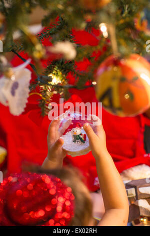 Little girl holding snow globe ornament in hand - Stock Photo