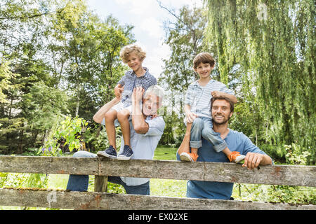 Portrait of three generation family males in garden - Stock Photo