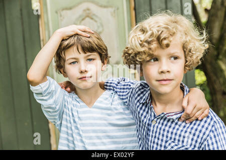 Portrait of two young brothers in garden - Stock Photo