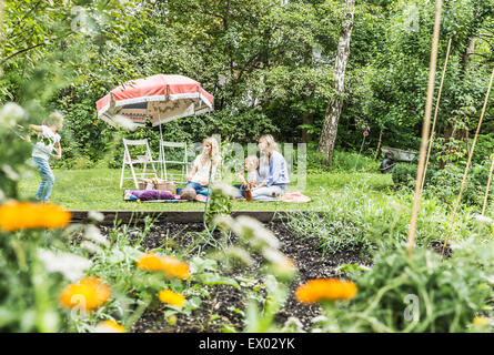 Two women and two girls picnicing in garden - Stock Photo