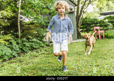 Boy running with dog in garden - Stock Photo