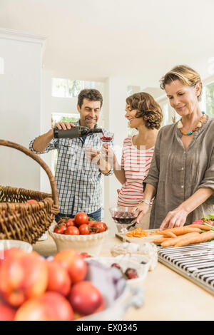 Three adults pouring red wine whilst preparing fresh vegetables - Stock Photo