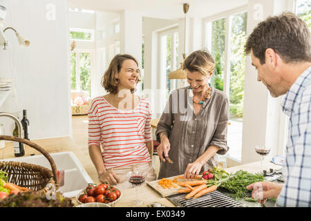 Three adults chatting whilst preparing fresh vegetables in kitchen - Stock Photo