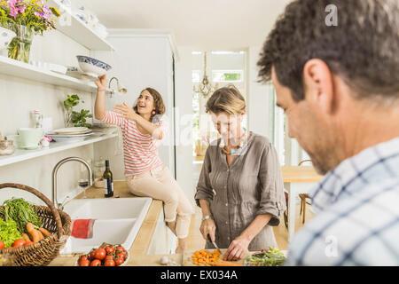 Three adults preparing fresh vegetables in kitchen - Stock Photo