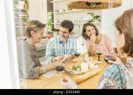 Adult friends drinking red wine and playing cards at dining table - Stock Photo
