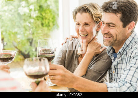 Couple toasting with red wine at dining table - Stock Photo
