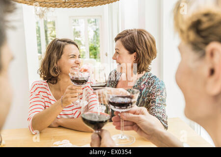 Four adult friends making a red wine toast at dinner - Stock Photo