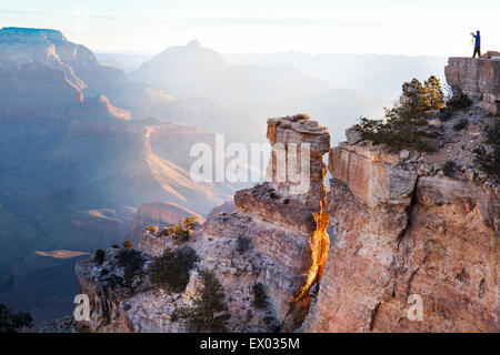 Distant silhouetted view of woman taking photographs of Grand Canyon, Arizona, USA - Stock Photo