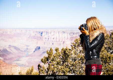 Woman taking photographs of Grand Canyon, Arizona, USA - Stock Photo