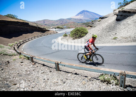 Male cyclist cycling up winding road, Tenerife, Canary Islands, Spain - Stock Photo