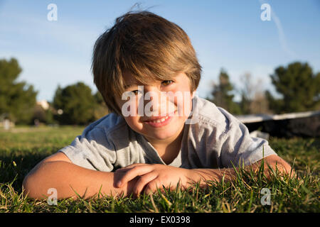 Portrait of smiling boy lying on park grass - Stock Photo