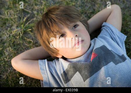 Portrait of boy lying on park grass gazing up - Stock Photo