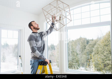 Young man installing ceiling light Stock Photo