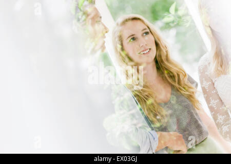 Looking through window at adults chatting in dining room - Stock Photo