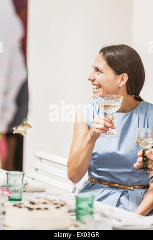 Young woman drinking wine at party - Stock Photo