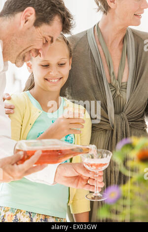 Mature man pouring wine at family party - Stock Photo