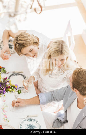 Overhead view of three adults chatting at birthday party in dining room - Stock Photo