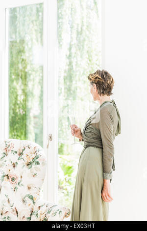 Portrait of senior woman looking out of window in living room - Stock Photo