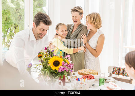 Girl hugging grandmother at birthday party - Stock Photo