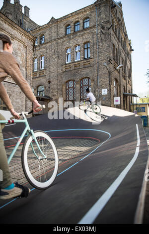Male and female cyclists racing uphill on city velodrome, Riga, Latvia - Stock Photo