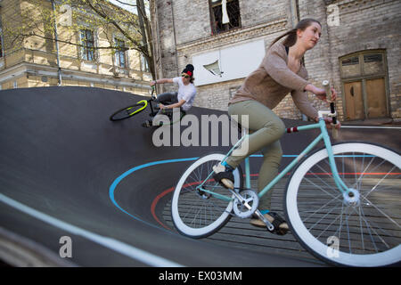 Male and female cyclists racing downhill on city velodrome, Riga, Latvia - Stock Photo