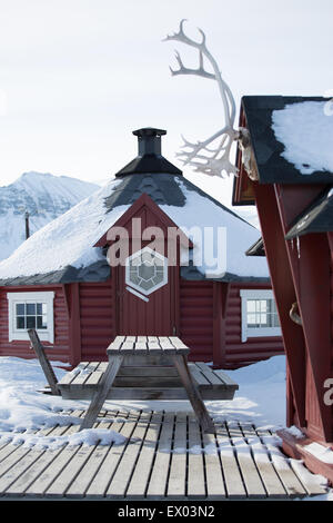 Traditional wooden house and picnic bench in snow, Longyearbyen,  Svalbard, Norway - Stock Photo
