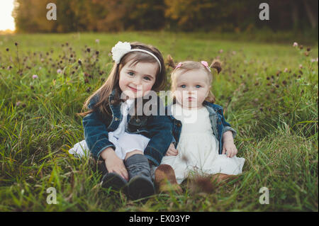 Portrait of young girl and baby sister in field
